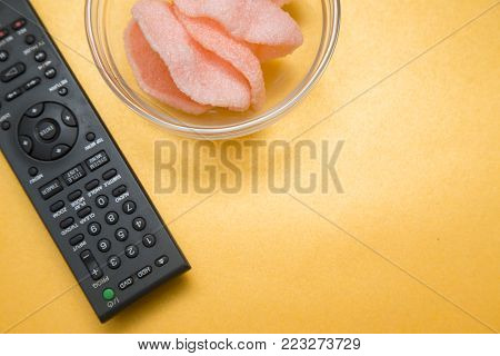 Weekend, Leisure, Hobby Concept. Weekend with movies, a remote control and shrimp chips on a light orange background, flat lay
