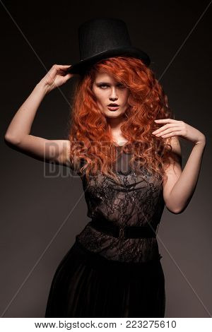 Studio portrait of beautiful redhead woman with freckles wearing black retro dress and black bowler hat on dark background