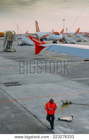 Milan Malpensa, Italy - November 21st, 2017: Airport personnel and rows of Easyjet Airbus A320 airplanes at Milan Malpensa airport tarmac. Airliner services short-haul flights in Europe