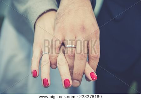 Wedding couple holding hands. Bride and groom's hands with wedding rings, close up.