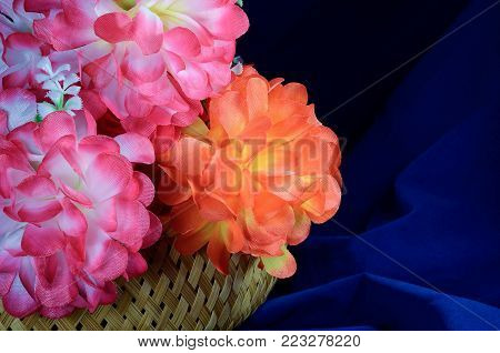 Bouquet of Artificial flower rose peony red white yellow and orange bright color made of synthetic fabric and plastic. Flowers lie in a wooden basket on table on dark blue fabric. Objects close up.