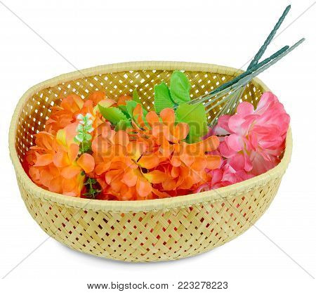 Bouquet in a basket of Artificial flower rose peony red white yellow and orange bright color made of synthetic fabric and plastic. Items pictured close up isolated on white background.