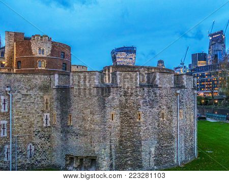 LONDON, ENGLAND - NOVEMBER 27, 2017: Old and new together in London. View at dusk time, wall of the Royal Palace Fortress, Tower of London and skyscrapers on the north bank of the River Thames.