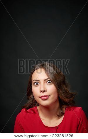 Surprised woman in red shirt and wavy hair looking up at blank copy space, over dark background