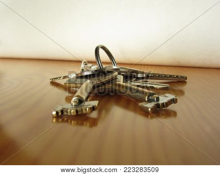 Bunch of worn house keys on wooden table
