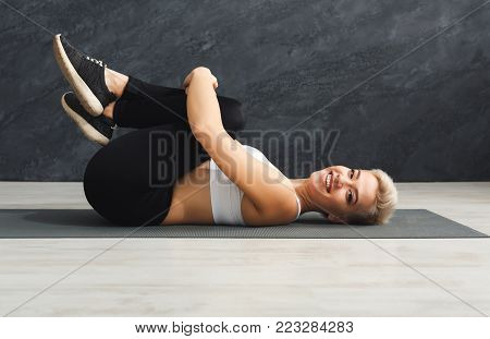 Happy fitness woman warmup stretching training at grey background indoors. Young slim girl making aerobics exercise, copy space