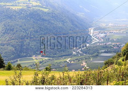 Chairlift, apple trees and mountain panorama in Algundo, South Tyrol
