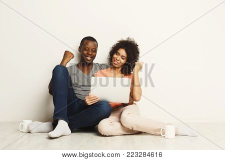 Happy african-american couple gambling online on laptop and winning. Succuess and online gaming concept, copy space, isolated