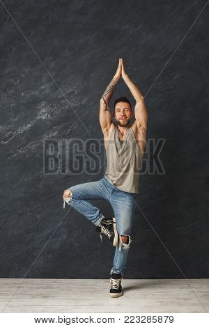 Happy handsome smiling man with tatoos making a yoga pose. Fashion boy at grey background, studio shot, copy space.