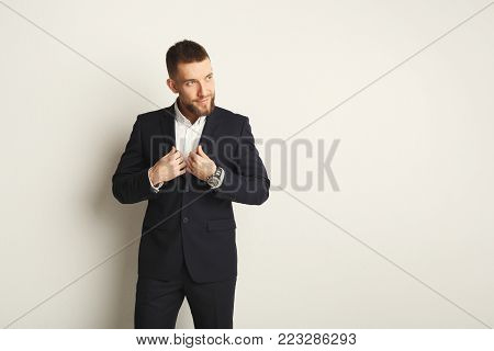 Handsome young caucasian businessman posing in studio and looking aside on white background. Confident serious man in formal clothes, copy space, isolated