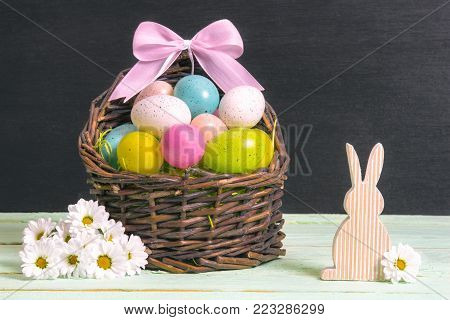 Bouquet of daisies and an Easter basket - Wicker basket full of multicolored Easter eggs and a pink bow, surrounded by white daisies and a wooden bunny, on a table and a black wall.