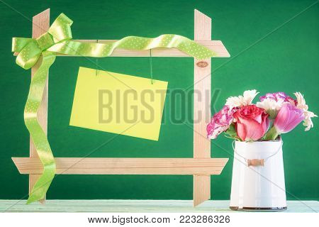 Flowers and frame with message card - Bouquet of flower in a vintage white bucket near a wooden frame decorated with a green ribbon and a tied bow with a blank message card hanging.