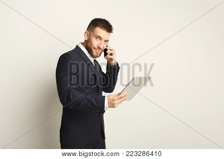 Handsome young caucasian businessman using digital tablet and talking on mobile on white background. Confident serious man in formal clothes, copy space, isolated