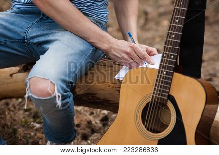 Guitar advertisement forest man idea concept. Creating masterpiece lyrics. Working process.
