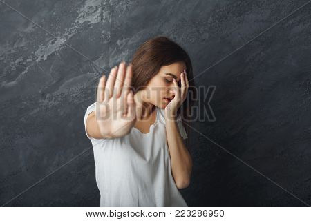 Attractive woman saying thanks but no. Beautiful girl denying proposal, making stop gesture with her hand, looking away, copy space
