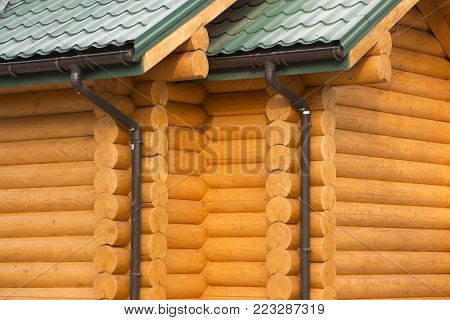 Gutter on a wooden house with a roof of green bituminous roofing.