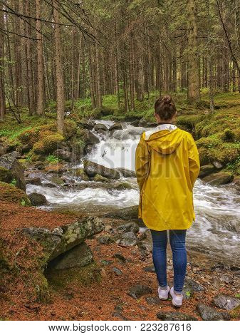 A woman in a yellow raincoat standing infront of the Rio di San Pellegrino in the Dolomites, Italy