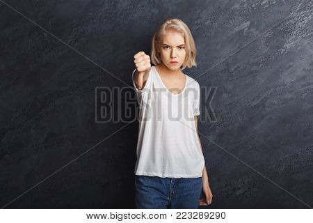 Unhappy girl gesturing failure with showing thumb down over dark studio background, copy space