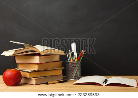 Educational background. Books pile, pencils, apple and open notebook against empty classroom blackboard for copy space. Back to school concept