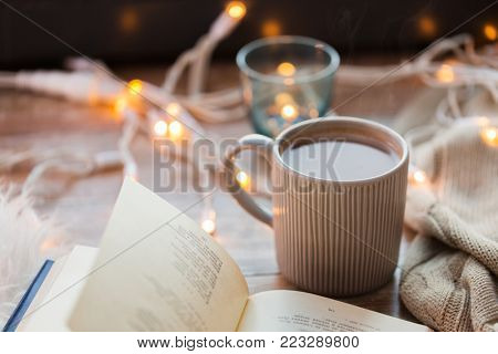 hygge and cozy home concept - book and cup of coffee or hot chocolate on table