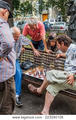 SOFIA, BULGARIA - JULY 15, 2017: Unidentified men play chess on a bench at the National Theater Garden
