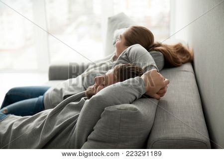 Relaxed couple asleep resting or having nap sitting on comfortable sofa enjoying daytime doze on weekend, calm carefree man and woman relaxing sleeping leaning on couch in cozy living room together