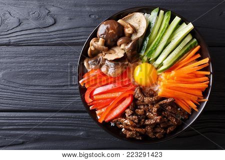 Korean Healthy Food Bibimbap Of Rice With Fried Beef, Raw Egg, Vegetables, Shiitake Close-up In A Bo