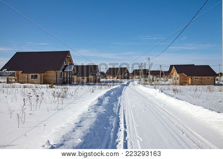 Landscape of village with wooden cottages in sunny winter day.