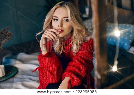 Sexy Fashion Blonde Woman In The Red Sweater Sitting On The Bed And Smiles. Glowing Garland At Home.