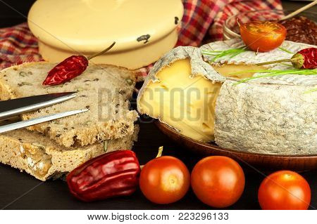 Domestic mature mold cheese with tomatoes. Dairy product. Aromatic cheese with mold