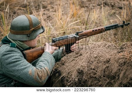 Gomel, Belarus - November 26, 2017: German soldier Wehrmacht in the trench with a Soviet automatic rifle