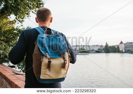 A tourist man with a backpack stands next to the river on the background of houses in Prague in the Czech Republic in Europe. Travel, leisure, tourism