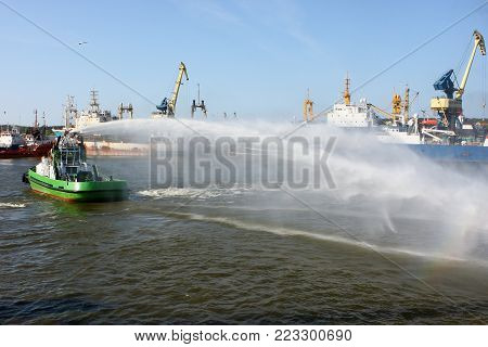 A floating modern tug boat sprays jets of water, demonstrates firefighting water cannon.
