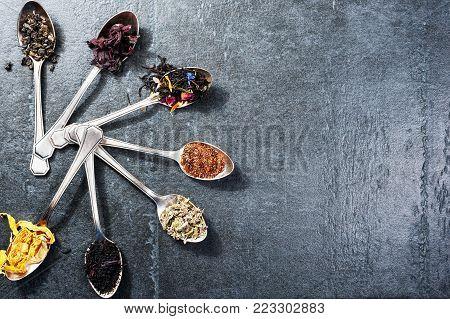 Various kinds of tea in spoons on dark slate background. Dry Tea assortment. Copyspace.