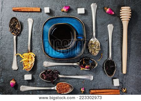 Assortment of dry tea and cup of hot tea. Green, black, green tea, rooibos, dry rose buds in spoons. Black textured slate background. Top view.