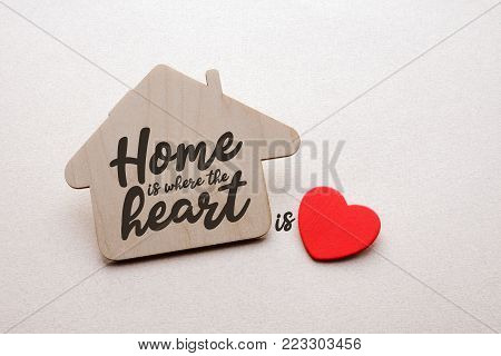 wooden house with written text, and red heart over white paper background, home ia where the heart is concept