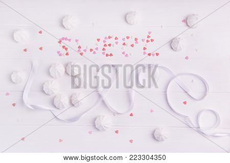Sweet Love lettering by white ribbon, merengue sweets and multicolor candies in shape of heart on the white wooden background. Love expression. Valentine's day