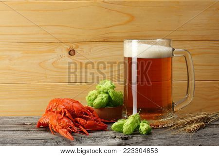 Glass beer with crawfish, hop cones and wheat ears with light wooden background. Beer brewery concept. Beer background