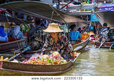 RATCHABURI, THAILAND - AUGUST 14: This is a boat seller in Damnoen Saduak floating market which is selling exotic fruits which are popular in Thailand on August 14, 2017 in Ratchaburi