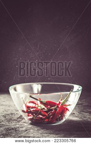 Red hot chilli pepper paprika in glass transparent bowl on stone table Ingredient for Mexican cooking Trendy toned image in rustic style