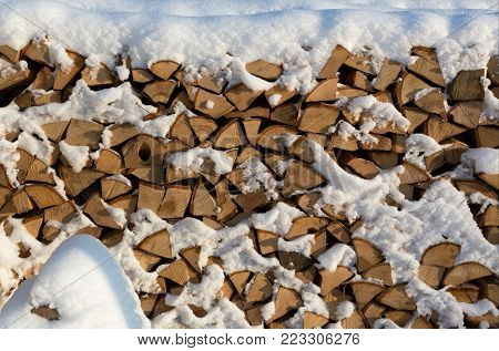 Firewood put. Chipped firewood. Firewood covered with snow.
