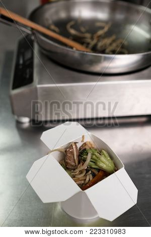 A box with Asian takeaway food on the top of the metal surface. Quick and convenient restaurant delivery