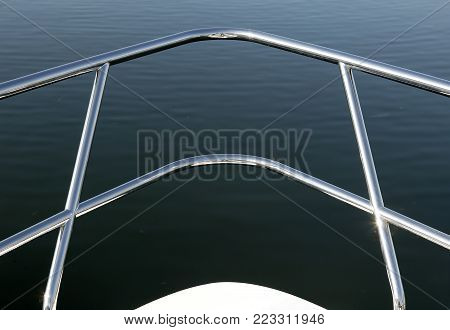 CHROME HAND RAIL ON BOW OF BOAT IN CLOSE UP