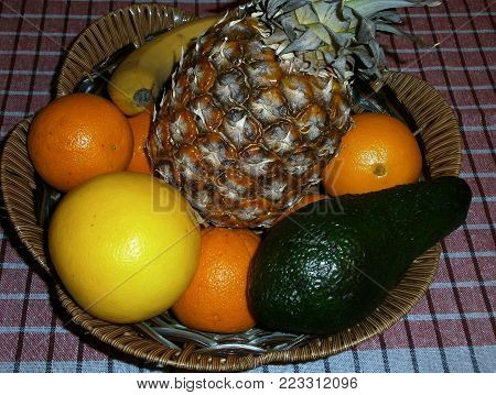 Fruit with basket.A basket on a table with delicious fruits as a background.