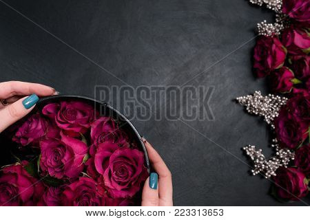 Romantic wedding flowers decor. Dark red or burgundy roses with silver adornment on black background. Bold, daring , alternative , and luxury reception party flower arrangement
