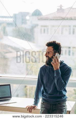 Small break from office work to catch up with a friend on the mobile. Smiling casual man standing near the window and talking on the phone with a client or business partner. Communication concept