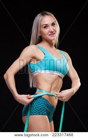 Athletic slim woman measuring her waist by measure tape after a diet over black background.