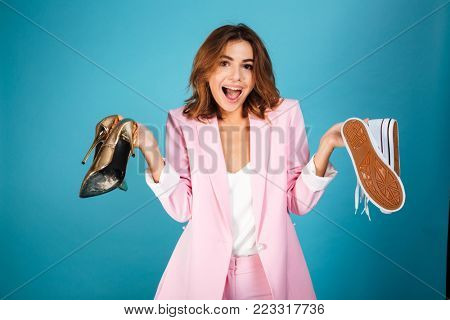 Portrait of a cheerful woman dressed in pink suit holding pair of high heels shoes and pair of sneakers isolated over blue background