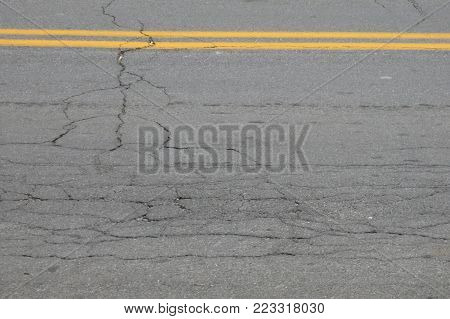 cracked asphalt of road with double yellow lines