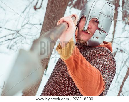 Medieval Irish warrior in chain mail and helmet holds a spear in the winter forest